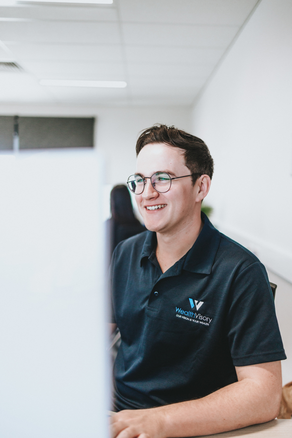 Andrew, WealthVisory's Office Assistant, smiling while working on client's business financial report
